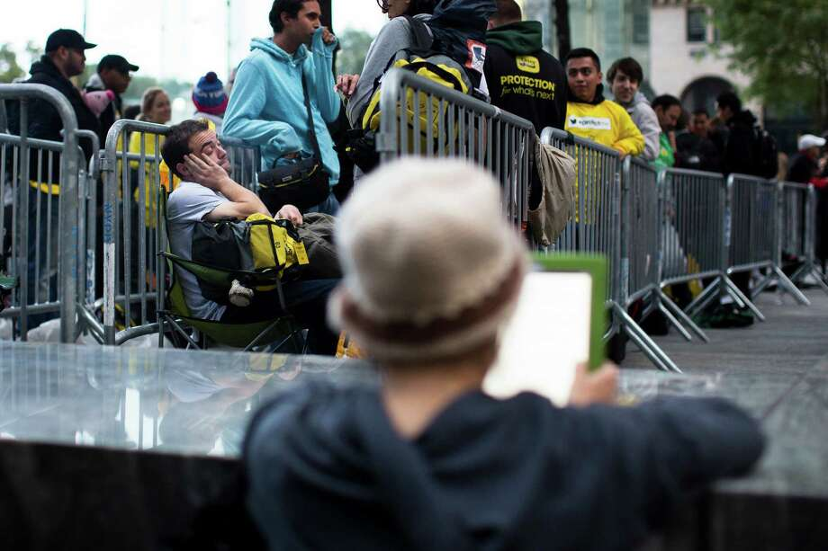 Consumers wait in line outside the Fifth Avenue Apple store for the imminent release of the iPhone 5, Friday, Sept. 21, 2012, in New York. Hundreds of people waited in line through the early morning to be among the first to get their hands on the highly anticipated phone. (AP Photo/John Minchillo) Photo: John Minchillo, Associated Press / FR170537 AP