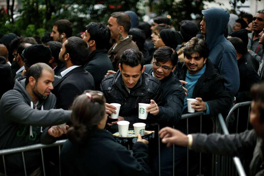 People are given cups of coffee as they queue up in Hanover Square to buy Apple iPhone 5 handsets at the company's store on nearby Regent Street in London, Friday, Sept. 21, 2012. In a now familiar global ritual, Apple fans jammed shops Friday to pick up the tech juggernaut's latest iPhone.  The smartphone is being launched in the U.S., Britain, Canada, France and Germany. It will go on sale in 22 more countries a week later. (AP Photo/Matt Dunham) Photo: Matt Dunham, Associated Press / AP