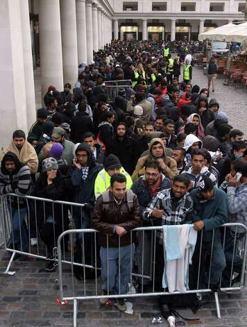 Customers queue to try and purchase the newly released Apple iPhone 5 at the company's store in Covent Garden, London, Friday, Sept. 21, 2012. In a now familiar global ritual, Apple fans jammed shops Friday to pick up the tech juggernaut's latest iPhone. The smartphone is being launched in the U.S., Britain, Canada, France and Germany. It will go on sale in 22 more countries a week later. (AP Photo/PA, Lewis Whyld) UNITED KINGDOM OUT, NO SALES, NO ARCHIVE Photo: Lewis Whyld, Associated Press / PA