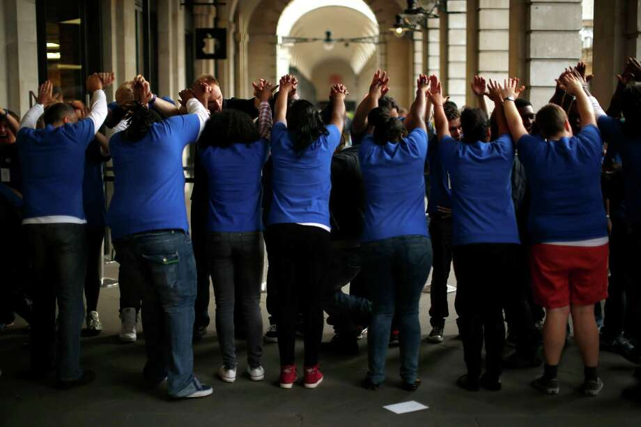 Apple employees form an arch for customers to run through as they enter the company's store in Covent Garden to purchase an iPhone 5, London, Friday, Sept. 21, 2012. In a now familiar global ritual, Apple fans jammed shops Friday to pick up the tech juggernaut's latest iPhone.  The smartphone is being launched in the U.S., Britain, Canada, France and Germany. It will go on sale in 22 more countries a week later. (AP Photo/Matt Dunham) Photo: Matt Dunham, Associated Press / AP