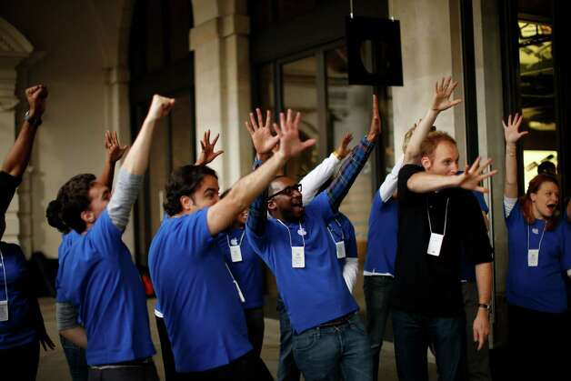 Apple workers gesture with five figners at customers leaving their store after purchasing iPhone 5 handsets in Covent Garden, London, Friday, Sept. 21, 2012. In a now familiar global ritual, Apple fans jammed shops Friday to pick up the tech juggernaut's latest iPhone.  The smartphone is being launched in the U.S., Britain, Canada, France and Germany. It will go on sale in 22 more countries a week later. (AP Photo/Matt Dunham) Photo: Matt Dunham, Associated Press / AP