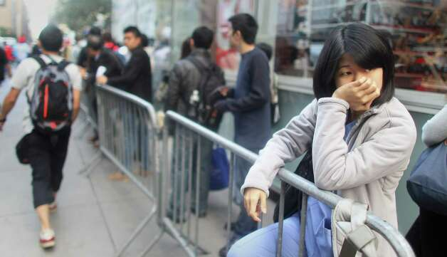 NEW YORK, NY - SEPTEMBER 21:  Nurse Angelie Mok waits on line to purchase the Apple iPhone 5 outside the Apple Fifth Avenue flagship store on the first morning it went on sale on September 21, 2012 in New York City. Customers lined up for days to purchase the hotly anticipated device which went on sale nationwide today. Photo: Mario Tama, Getty Images / 2012 Getty Images