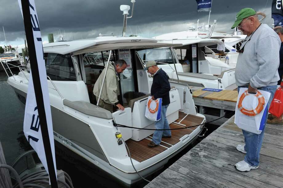 Bill Chanberlain of Orange, center, and his friend Ed Bardy, right, Monroe, looking at the boats at the Norwalk Show Thursday, Sept. 20, 2012. The Norwalk Boat Show, a in-water boat show, runs Thursday through Sunday September 20-23, 2012 10am-6pm daily. Photo: Helen Neafsey / Greenwich Time