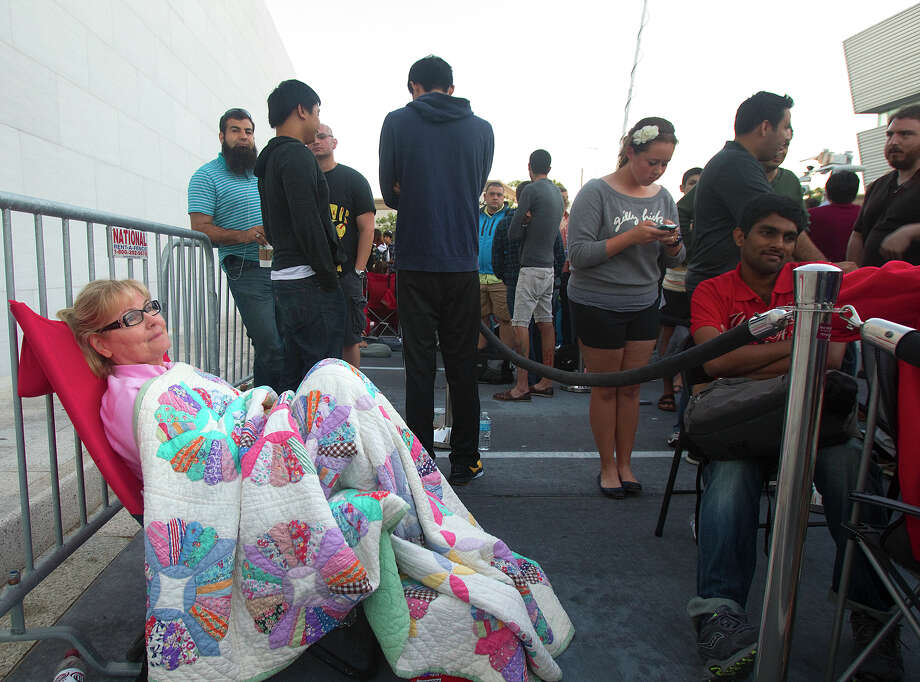 """Cheryl Thomas, left, lays in a chair as she waits in line for the release of the iPhone 5 outside the Apple Store on Westheimer Friday, Sept. 21, 2012, in Houston. """"I'm interested in the picture piece,"""" she said of the new camera functions. She also said she's looking forward to Siri. Photo: Cody Duty, Houston Chronicle / © 2012 Houston Chronicle"""