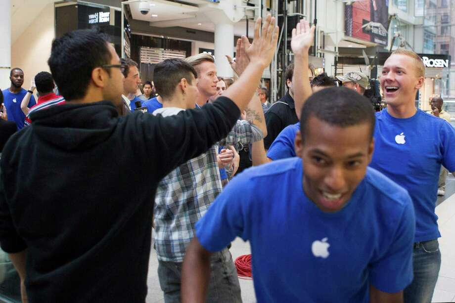 Apple staff high five customers as they queue to buy the new Apple iPhone 5 at the Apple store in Toronto's Eaton Centre on Friday Sept. 21 2012.  (AP Photo/The Canadian Press, Chris Young) Photo: Chris Young, Associated Press / The Canadian Press
