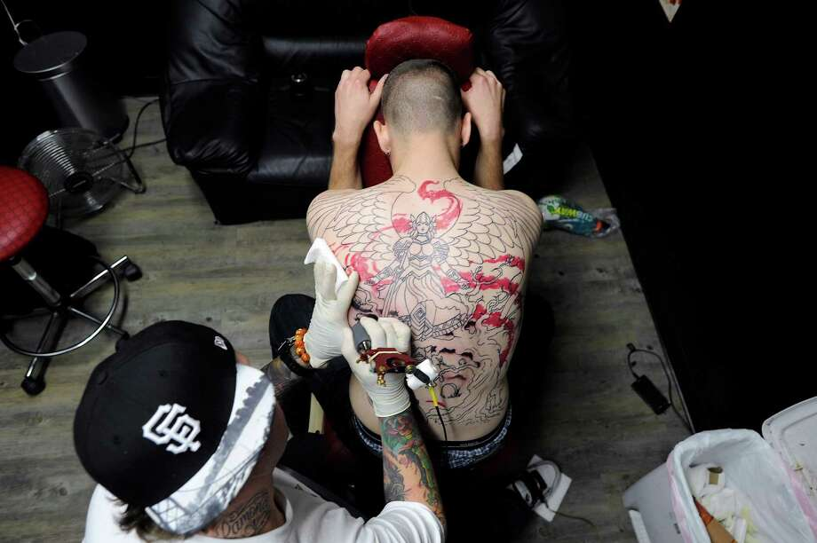 Brown works on large back piece on Daniel Chambers of Sunnyvale. Photo: Michael Short, Special To The Chronicle / ONLINE_YES