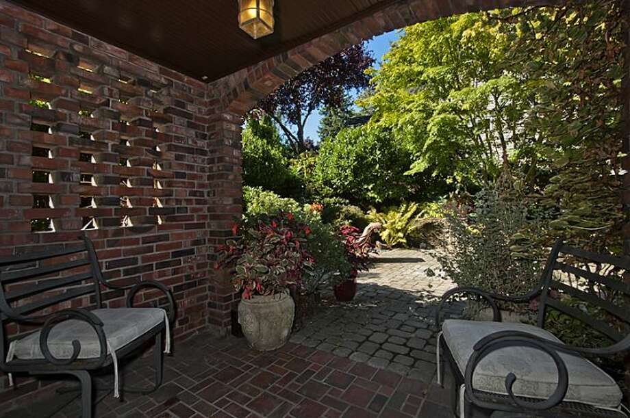 Patio of 335 36th Ave E. The 2,580-square-foot brick Tudor, built in 1930, has with three bedrooms and 3.25 bathrooms -- including a master suite with a walk-in closet -- a loft, leaded-glass windows, French doors, exposed-wood moldings and beamed ceilings, an updated kitchen and a two-car garage on a 5,587-square-foot lot. It's listed for $1.1 million. Photo: Courtesy John Coake And Mark Dickerman/Windermere Real Estate