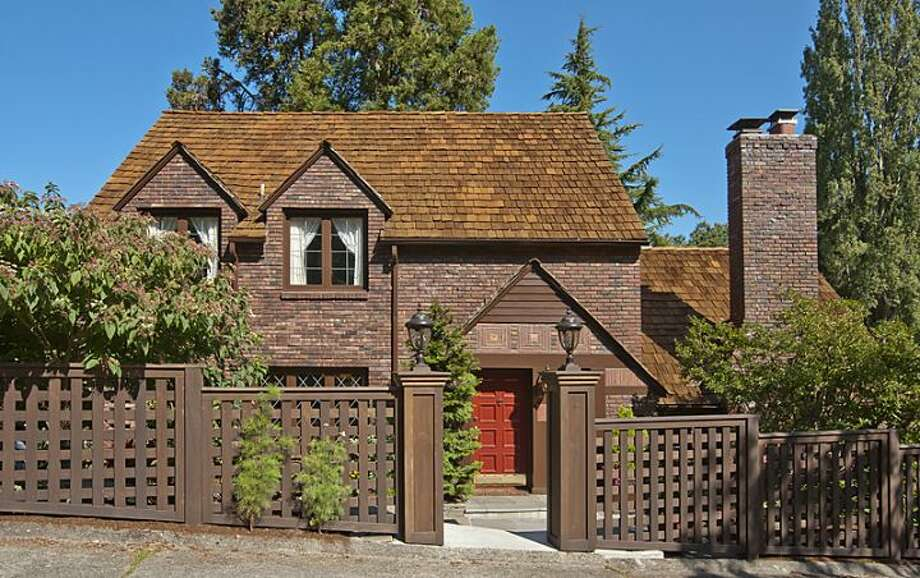 Exterior of 335 36th Ave E. The 2,580-square-foot brick Tudor, built in 1930, has with three bedrooms and 3.25 bathrooms -- including a master suite with a walk-in closet -- a loft, leaded-glass windows, French doors, exposed-wood moldings and beamed ceilings, an updated kitchen, a large patio and a two-car garage on a 5,587-square-foot lot. It's listed for $1.1 million. Photo: Courtesy John Coake And Mark Dickerman/Windermere Real Estate