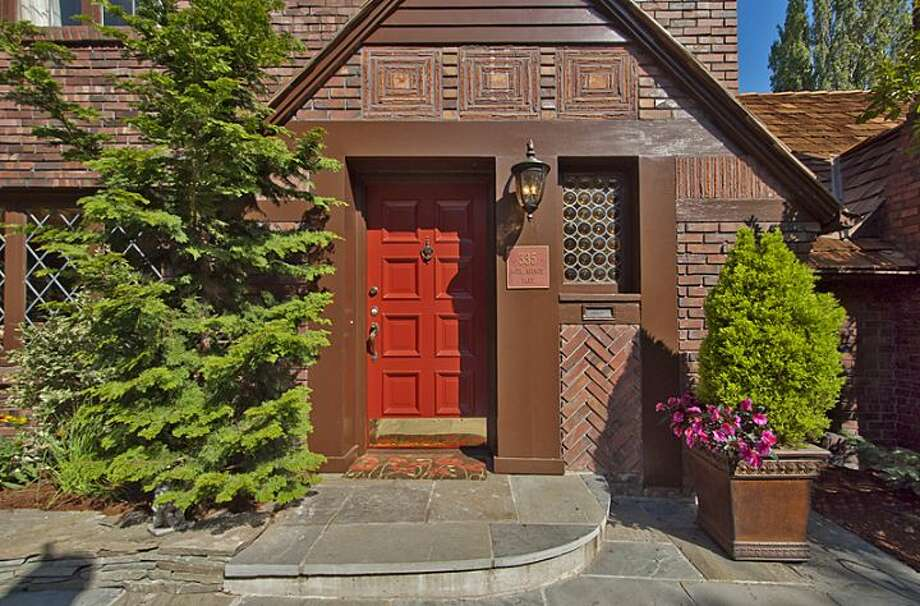 Front door of 335 36th Ave E. The 2,580-square-foot brick Tudor, built in 1930, has with three bedrooms and 3.25 bathrooms -- including a master suite with a walk-in closet -- a loft, leaded-glass windows, French doors, exposed-wood moldings and beamed ceilings, an updated kitchen, a large patio and a two-car garage on a 5,587-square-foot lot. It's listed for $1.1 million. Photo: Courtesy John Coake And Mark Dickerman/Windermere Real Estate