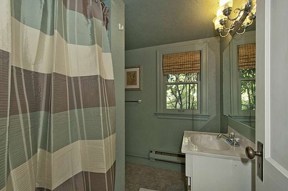 Bathroom of 335 36th Ave E. The 2,580-square-foot brick Tudor, built in 1930, has with three bedrooms and 3.25 bathrooms -- including a master suite with a walk-in closet -- a loft, leaded-glass windows, French doors, exposed-wood moldings and beamed ceilings, an updated kitchen, a large patio and a two-car garage on a 5,587-square-foot lot. It's listed for $1.1 million. Photo: Courtesy John Coake And Mark Dickerman/Windermere Real Estate