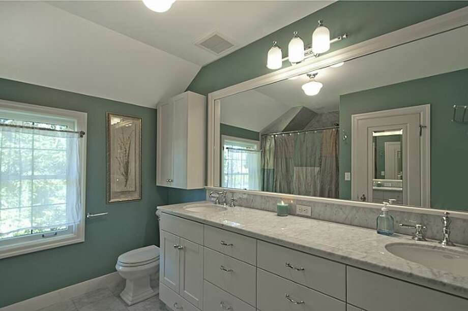 Master bathroom of 335 36th Ave E. The 2,580-square-foot brick Tudor, built in 1930, has with three bedrooms and 3.25 bathrooms, a loft, leaded-glass windows, French doors, exposed-wood moldings and beamed ceilings, an updated kitchen, a large patio and a two-car garage on a 5,587-square-foot lot. It's listed for $1.1 million. Photo: Courtesy John Coake And Mark Dickerman/Windermere Real Estate