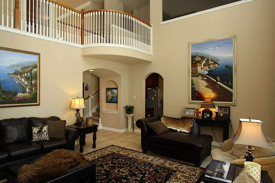 High ceilings and an overlooking balcony contribute to the spacious feel of the home's living area. Photo: DM