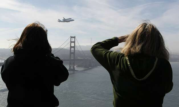 Nancy Crain (left) and Susette Stickel-Rufer take photos from the Marin Headlands in Sausalito, Calif.,  as the space shuttle Endeavour flies above the Golden Gate Bridge on its final flight before landing in Los Angeles on Thursday, Sept. 20, 2012. Photo: Paul Chinn, The Chronicle
