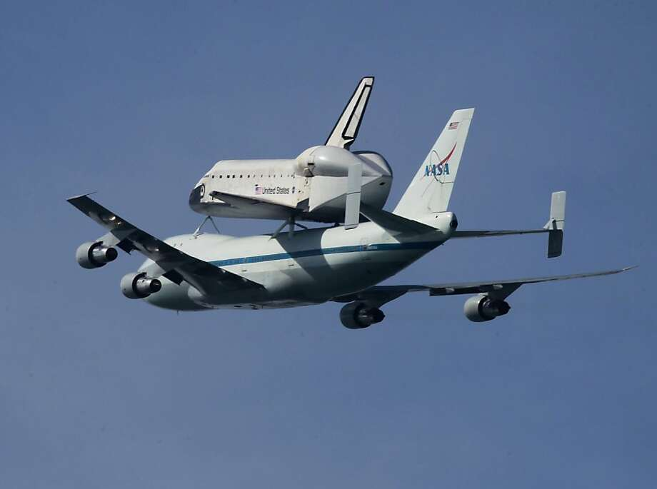 Mounted on top of a NASA transporter, the space shuttle Endeavour flies above the Golden Gate Bridge past the Marin Headlands in Sausalito, Calif. on Thursday, Sept. 20, 2012. Photo: Paul Chinn, The Chronicle