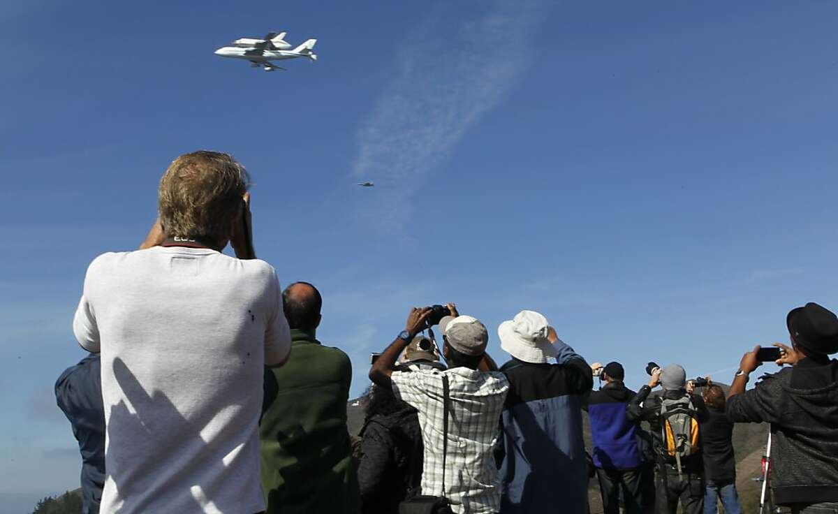 Enthusiasts snap photographs as the space shuttle Endeavour flies near the Golden Gate Bridge past the Marin Headlands in Sausalito, Calif. on Thursday, Sept. 20, 2012.