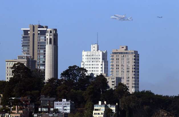 The Space Shuttle Endeavour with Coit Tower in the foreground as it flew over the Bay Area on Friday, September 21, 2012, in San Francisco, Calif., on its farewell voyage before it is converted to a museum in Los Angeles. Photo: Carlos Avila Gonzalez - San Fran, The Chronicle