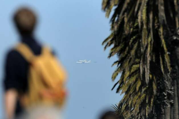 Spectator watches from Treasure Island as the Space Shuttle Endeavor to flies over the Bay Area on Friday, September 21, 2012, in San Francisco, Calif., on its farewell voyage before it is converted to a museum in Los Angeles. Photo: Carlos Avila Gonzalez, The Chronicle