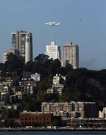 The Space Shuttle Endeavour with Coit Tower in the foreground as it flew over the Bay Area on Friday, September 21, 2012, in San Francisco, Calif., on its farewell voyage before it is converted to a museum in Los Angeles. Photo: Carlos Avila Gonzalez, The Chronicle