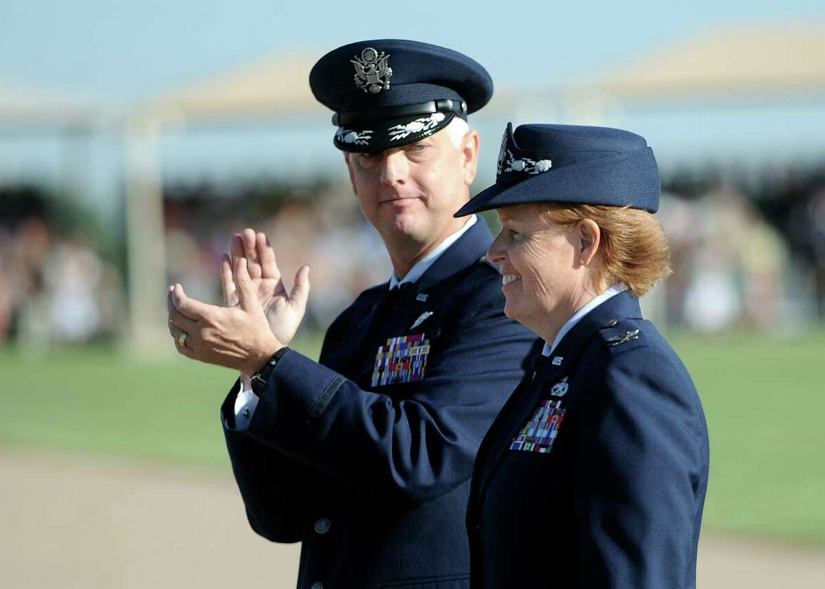 Col. Deborah Liddick, new commander of the Air Force basic training program at Lackland, is applauded by Col. Mark Camerer.