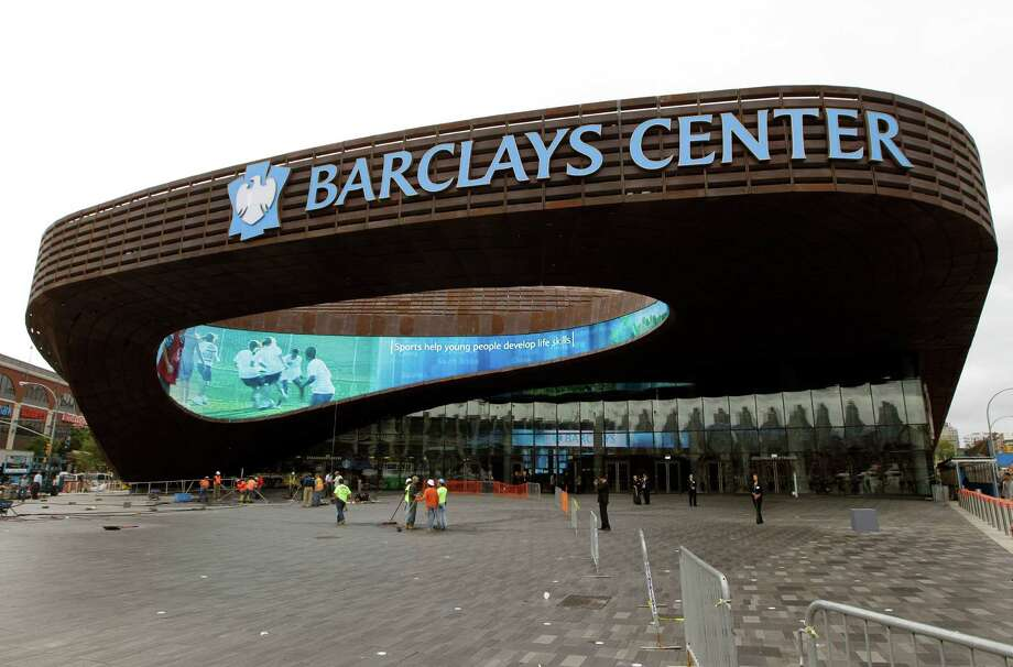 Workers sweep the plaza in front of the main entrance to the Barclays Center in the Brooklyn borough of New York, Thursday, Sept. 20, 2012, in preparation for Friday's ribbon-cutting ceremony. A new chapter in Brooklyn's history begins Friday when the Brooklyn Nets' new arena opens. Photo: Kathy Willens, AP / AP