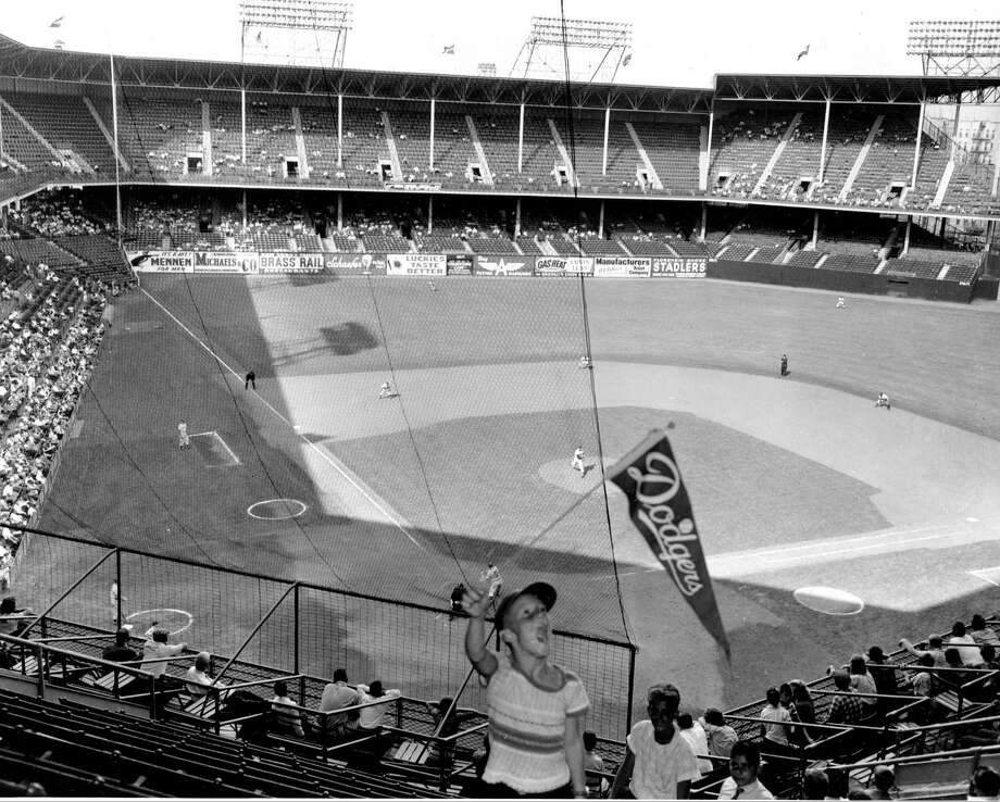 FILE - In this file photo of Sept. 22, 1957, two days before the Brooklyn Dodgers played their last game at Ebbets Field, a  young Dodgers fan waves a banner in the stadium as the Dodgers played the Philadelphia Phillies in Brooklyn, N.Y. It was like a death in the family for Brooklyn baseball fans when their beloved Dodgers left the borough behind for the California coast. But after decades without a professional sports team, Brooklyn is hitting the major leagues again on Friday, Sept. 21, 2012 when the Brooklyn Nets' new arena opens to the public. Photo: AP / AP