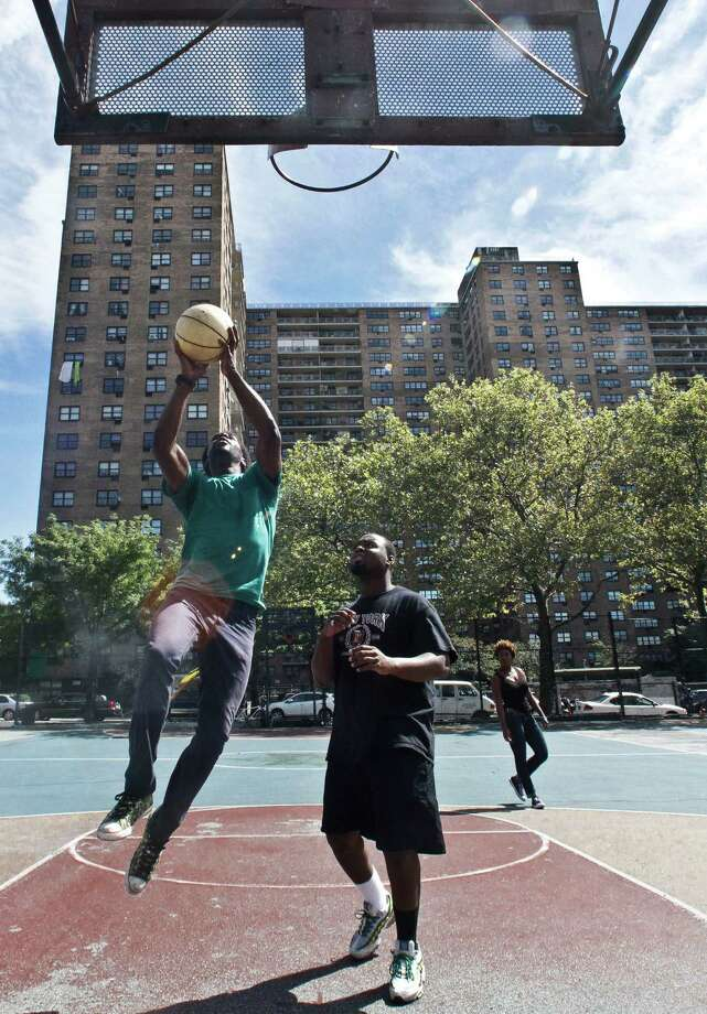 Eric Johnson, left, 19, and Mario Volcin, 23, play basketball in the Jackie Robinson Playground as the Ebbets Field apartments looms in the background, on Wednesday, Sept. 19, 2012 in Brooklyn, N.Y.  Ebbets Field, home to the Brooklyn Dodgers baseball decades ago, became a sprawling residential complex to thousands after the Dodgers moved west.  Now Brooklyn is hitting the major leagues again with a new arena and the Brooklyn Nets' NBA franchise. Photo: Bebeto Matthews, AP / AP