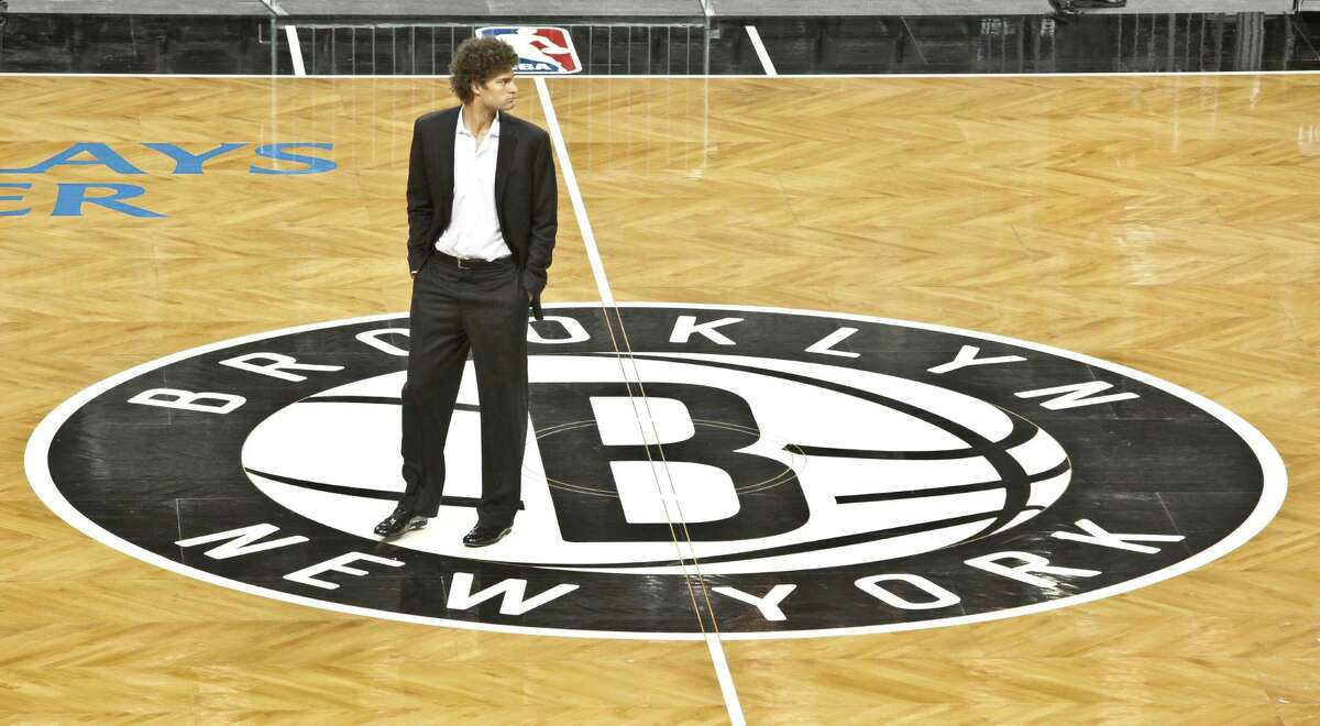 Brooklyn Nets basketball player Brook Lopez walks onto the floor of the Barclay's Center, Brooklyn's newest arena and the team's new home, after a ribbon cutting ceremony on Friday, Sept. 21, 2012 in New York. The ceremony marked the official unveiling of the arena, the first building that is part of the Atlantic Yards development in Brooklyn.