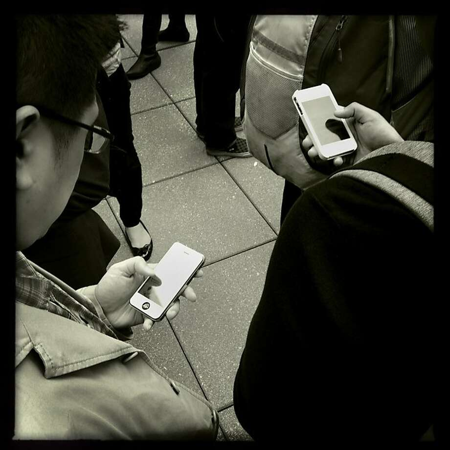 People use their smartphones. Photo: Mike Kepka, The Chronicle