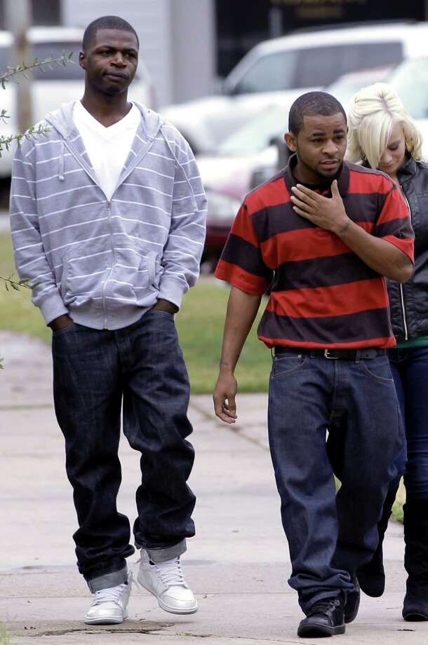 Rayford Tyrone Ellis Jr., right, and Timothy Daray Ellis, left, leave the Liberty County Courthouse after a status update in their cases Monday, Dec. 5, 2011, in Liberty, Texas. Both men are among more than a dozen men accused of taking part in a series of sexual assaults on an 11-year-old girl that horrified and divided their small Southeast Texas town that appeared in court Monday. The investigation began last year after one of the girl's friends told a teacher he had seen a lurid cell phone video that showed the girl being raped in an abandoned trailer. Also accused are six juvenile boys, three of whom have pleaded guilty. (AP Photo/David J. Phillip) Photo: David J. Phillip, Associated Press / AP
