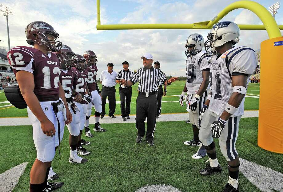 Head Referee Cliff Landry, center, gives instructions to both the Jaguars and the Mustangs Friday 14, 2012. There are two different moments that occur before the start of a football game involving the coin toss.  The actual coin toss occurs close to the end zone that is nearest the field house/locker rooms right after the players finish pre-game warmups. Coaches and a player or two from each team join the game officials for the toss that determines who gets the ball first and what side of the field the teams' will defend to start the game. The second toss occurs at midfield right before the game starts. This is really just a symbolic coin toss to let the spectators know who kicks off and receives to start the game. These decisions were already made in the earlier coin toss.   Dave Ryan/The Enterprise