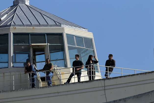 Spectators watch from the top of a building on Treasure Island as they wait for the Space Shuttle Endeavour to fly over the Bay Area on Friday, September 21, 2012, in San Francisco, Calif., on its farewell voyage before it is converted to a museum in Los Angeles. Photo: Carlos Avila Gonzalez - San Fran, The Chronicle