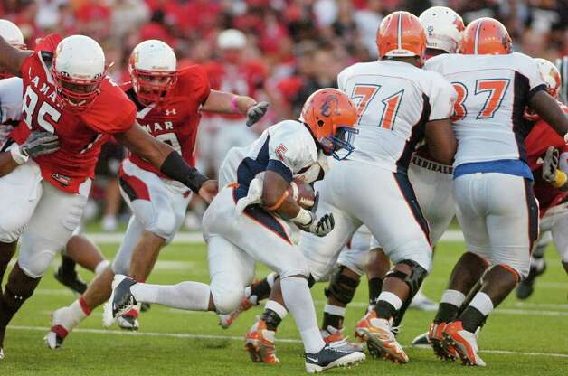 Lamar defensive lineman Adren Dorsey, left, and Mark Murrill, center, try to stop Langston University running back Carlos Ross (5) during the first half at Provost Umphrey Stadium. Saturday, October 9, 2010. Valentino Mauricio/The Enterprise Photo: Valentino Mauricio / Beaumont