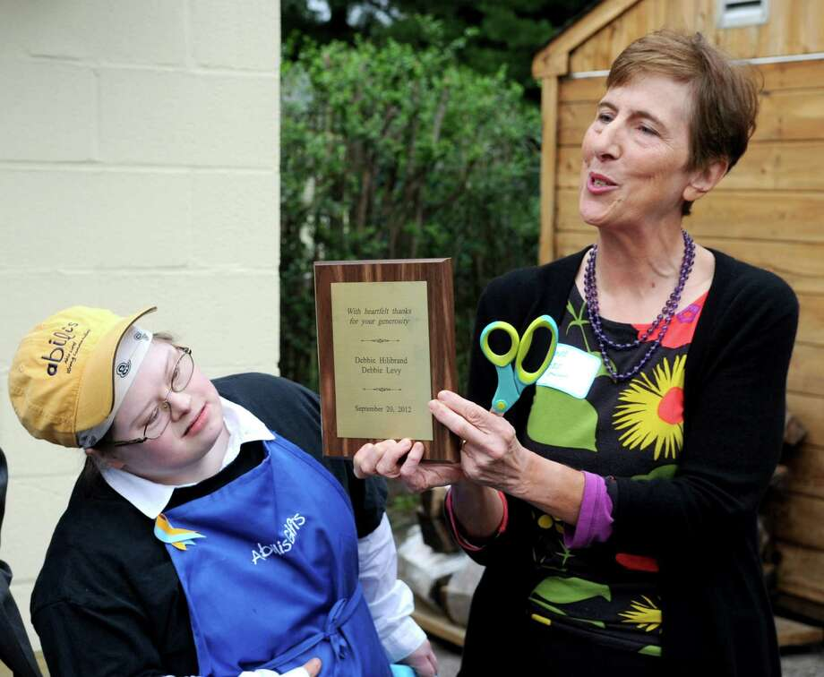 Executive Director Lolli Ross holds up a plaque as Susie Figgie leans to get a look during a grand-opening celebration for Abilis Gifts, a retail-store training site for adults with disabilities in Greenwich, on Thursday, September 20, 2012. Photo: Lindsay Niegelberg / Stamford Advocate