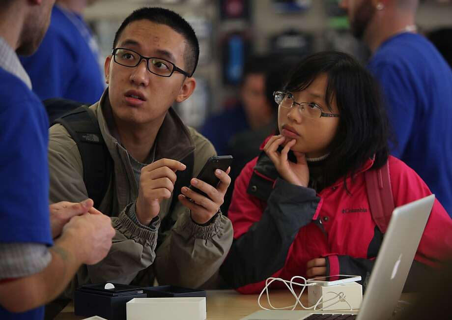 Kia Li (left) and Xiating Huang (right), recently moved here from China, getting familiar with their IPhone 5 at the Apple store on Chestnut Street in San Francisco, Calif., on Friday, September 21, 2012. Photo: Liz Hafalia, The Chronicle