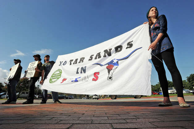 Members of the Tar Sands Blockade hold signs Wednesday at the Jefferson County Courthouse in protest of the Keystone Pipeline Project's attempt to claim property from landowners. The event was a precursor to litigation in Judge Tom Rugg's courtroom regarding a writ of possession filled by pipeline attorneys against several area landowners and rice farmers. Photo taken Wednesday, September 12, 2012 Guiseppe Barranco/The Enterprise Photo: Guiseppe Barranco, STAFF PHOTOGRAPHER / The Beaumont Enterprise