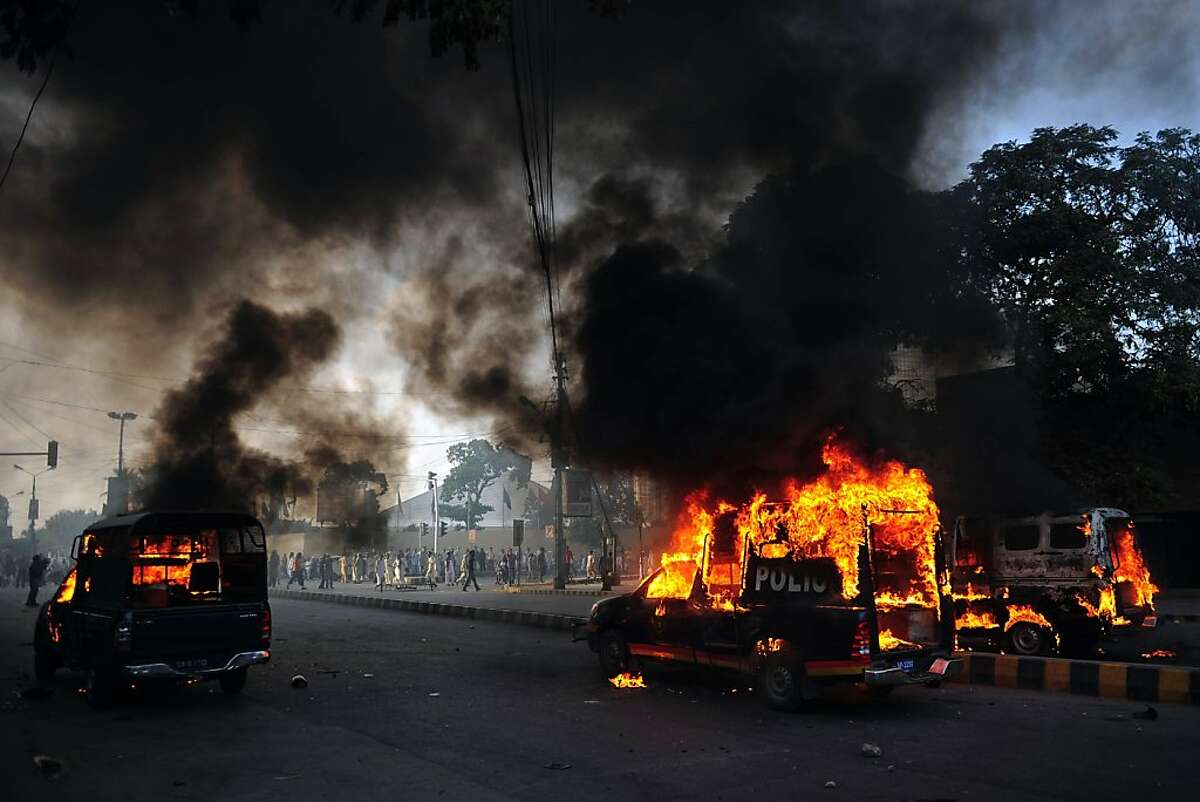 Smoke and flames rise from burning police vehicles torched by angry demonstrators during a protest against an anti-Islam film in Karachi on September 21, 2012. At least nine people died in Pakistan during violent protests on Friday condemning a US-made film insulting Islam, officials said. AFP PHOTO / ASIF HASSANASIF HASSAN/AFP/GettyImages