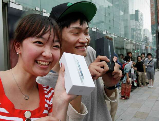 Kae Shibata 20, left, and Yutaro Noji, 21, show off Apple's iPhone 5 after they bought at a store in Tokyo Friday morning, Sept. 21, 2012. (AP Photo/Koji Sasahara) Photo: Koji Sasahara