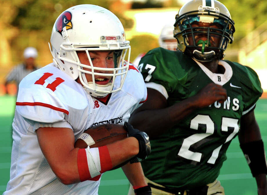 Greenwich's #11 Alex McMurray carries the ball as Bassick's #27 A.J. Brown looks to tackle, during football action in Bridgeport, Conn. on Friday September 21, 2012. Photo: Christian Abraham / Connecticut Post