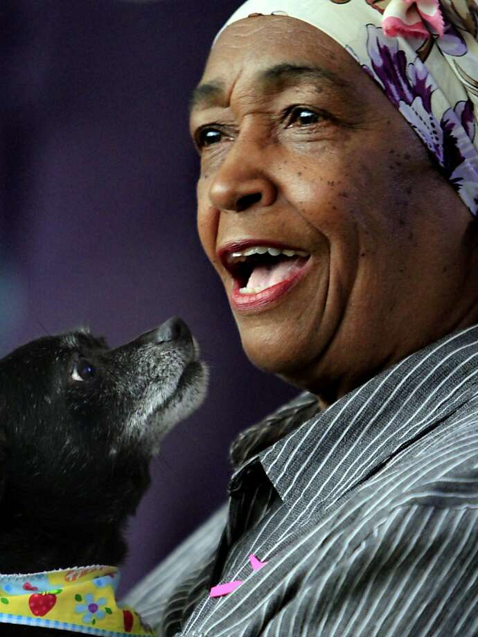 Jean Green sings a song to Chula, the dog she fostered with Eric Wightman, as she says goodbye at the Woof graduation. Photo: Sarah Rice, Special To The Chronicle