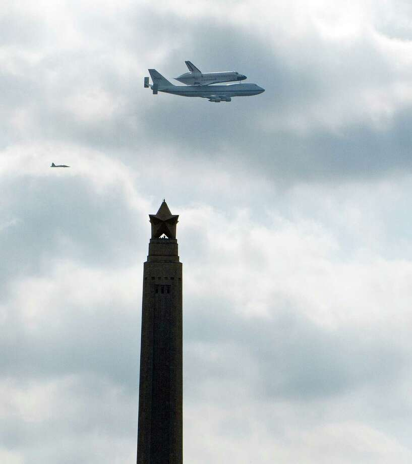 The space shuttle Endeavour rides atop a NASA 747 Shuttle Carrier Aircraft as it passes over the San Jacinto Monument Wednesday, Sept. 19, 2012, in La Porte. The shuttle is being ferried across the United States from the Kennedy Space Center to the California Science Center in Los Angeles. ( James Nielsen / Chronicle ) Photo: James Nielsen / © Houston Chronicle 2012