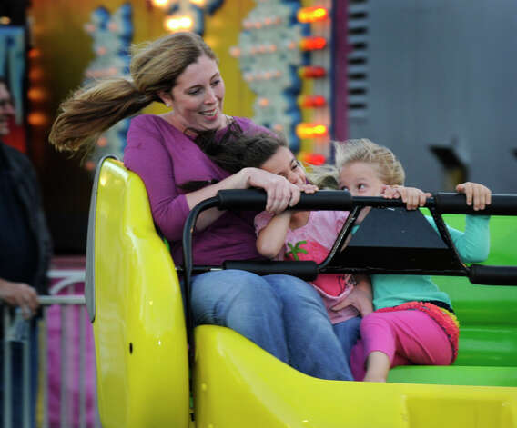 Taking a ride on the Sizzler, one of the rides at the Ridgefield Chamber of Commerce carnival, are from left, Amanda Pambianchi, daughter Natalie, 5, and a friend, Emily Seal, 5, Friday, Sept. 21, 2012. Photo: Carol Kaliff