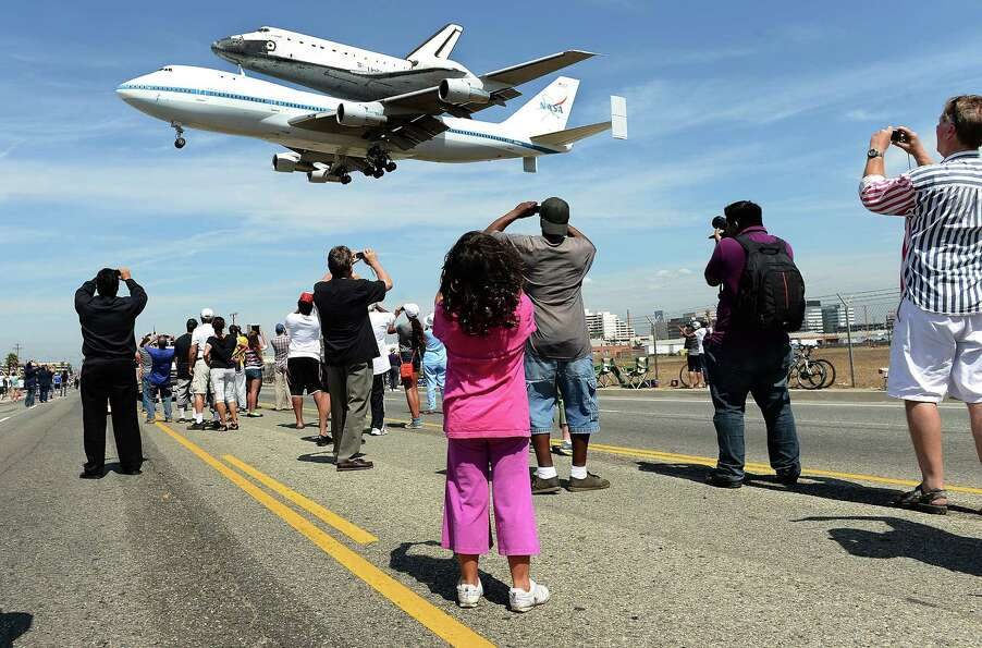 People stand along Aviation Blvd. as the space shuttle Endeavour lands at LAX Friday, September 21,