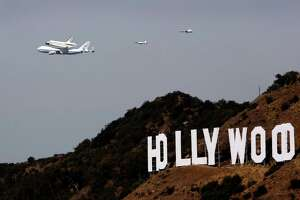 The space shuttle Endeavour passes the iconic Hollywood sign on Friday, September 21, 2012, in Los Angeles, California.