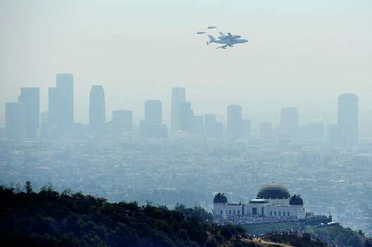 The Space Shuttle Endeavour, mounted atop NASA's modified Boeing 747, flies near the Griffith Park Observatory in Los Angeles on its final flight, September 21, 2012. The retired space shuttle is spending it's last day in the air on a 5-hour flyover before landing at the Los Angeles International Airport, where it will stay for a few weeks before taking a slow-speed land journey across town through neighborhoods to its final museum home, the California Space Center. Photo: JOE KLAMAR, AFP/Getty Images / AFP