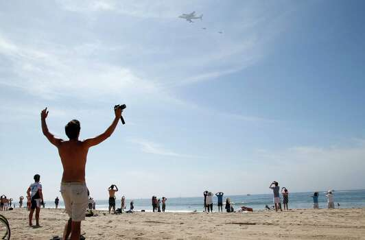 Spectators watch as the Space Shuttle Endeavour mounted on NASA's Shuttle Carrier Aircraft (SCA) flies near Santa Monica, Calif., Friday, Sept. 21, 2012. Photo: Jae C. Hong, Associated Press / AP