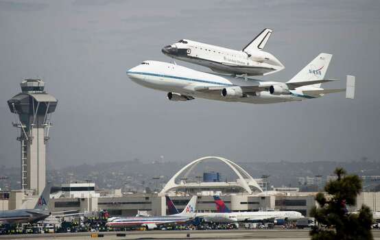 Space shuttle Endeavour, sitting on top of NASA's Shuttle Carrier Aircraft or SCA, flies over the Los Angeles International Airport on September 21, 2012 in Los Angeles.  The Space Shuttle Endeavour will be placed on public display at the California Science Center. This is the final ferry flight scheduled in the Space Shuttle Program era. Photo: Michal Czerwonka, Getty Images / 2012 Getty Images