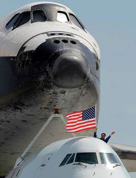 J.J. Johnston, FAA liasion and coordinator of all the Space Shuttle homecoming flights, waves the U.S. flag from the cockpit as the Space Shuttle Endeavour taxis to an airline maintenance hangar aboard a NASA Boeing 747, at the conclusion of its last flight at Los Angeles International Airport Friday, Sept. 21, 2012.  In a few weeks Endeavour will be towed through city streets to its new home at the California Science Center in downtown Los Angeles. Photo: Reed Saxon, Associated Press / AP