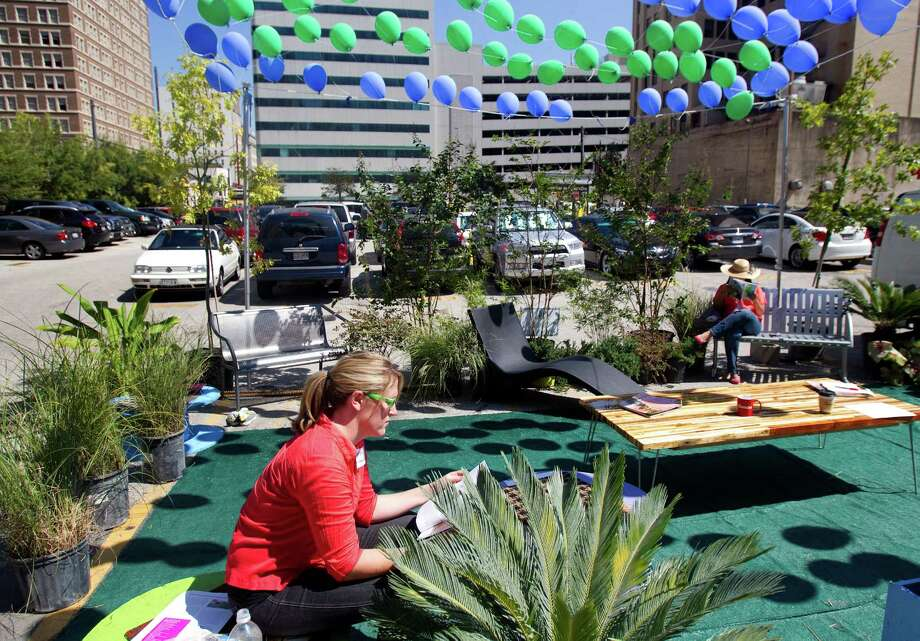 Kerri Da Silva, left, and Nubia Carino, right, sit in a converted parking spot during Park(ing) Day at a parking lot at the corner of Main and Capitol Streets Friday, Sept. 21, 2012, in Houston. The global event involves citizens, artists and activists that collaborate to temporarily convert a metered parking spot into a temporary public space. The organization's mission is to increase awareness for the need of more urban open space. (Cody Duty / Houston Chronicle) Photo: Cody Duty / © 2012 Houston Chronicle