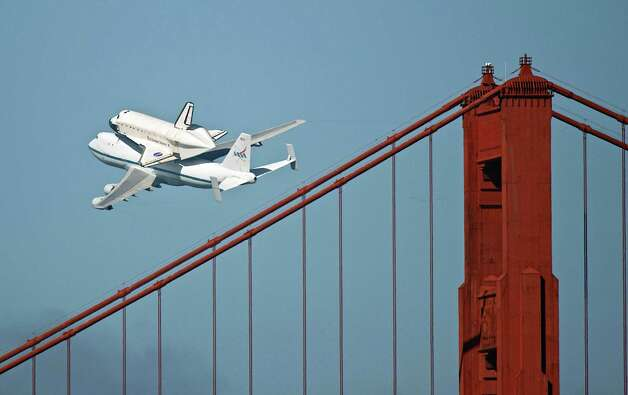 The space shuttle Endeavour passes over the Golden Gate Bridge in San Francisco, Friday, Sept. 21, 2012. Endeavour is making a final trek across the country to the California Science Center in Los Angeles, where it will be permanently displayed. (AP Photo/Michael Kass) Photo: Michael Kass