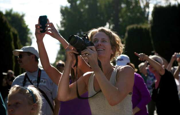 Karen Thiebaud, from Sacramento, makes pictures of the Space Shuttle Endeavour mounted on NASA's Shuttle Carrier Aircraft  as it flies over the Capitol dome in Sacramento, Calif. on Friday,  Sept. 21, 2012. (AP Photo/The Sacramento Bee, Sue Morrow)  MAGS OUT; LOCAL TV OUT (KCRA3, KXTV10, KOVR13, KUVS19, KMAZ31, KTXL40); MANDATORY CREDIT Photo: Sue Morrow